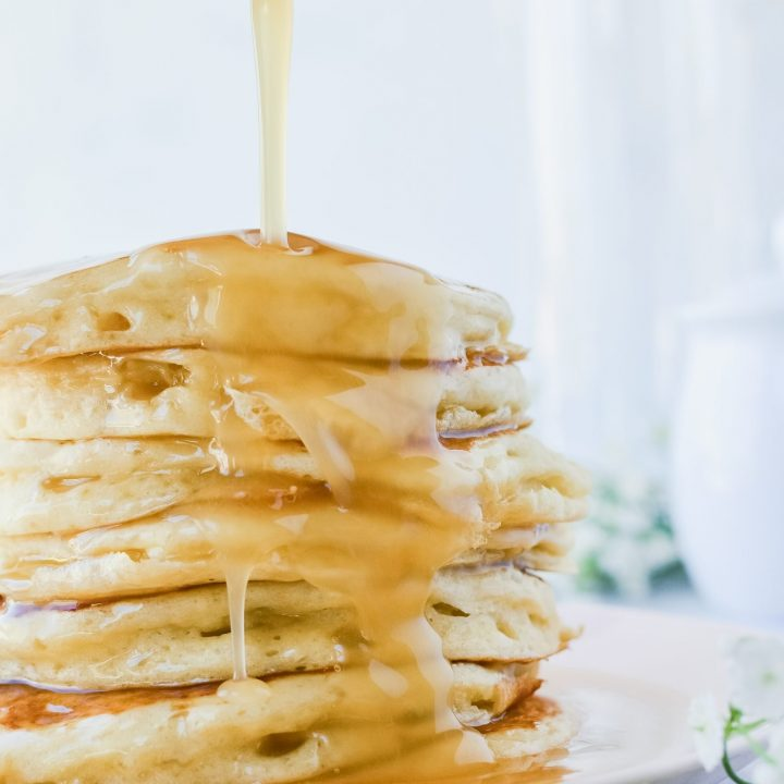 homemade buttermilk syrup poured over fluffy buttermilk pancakesp