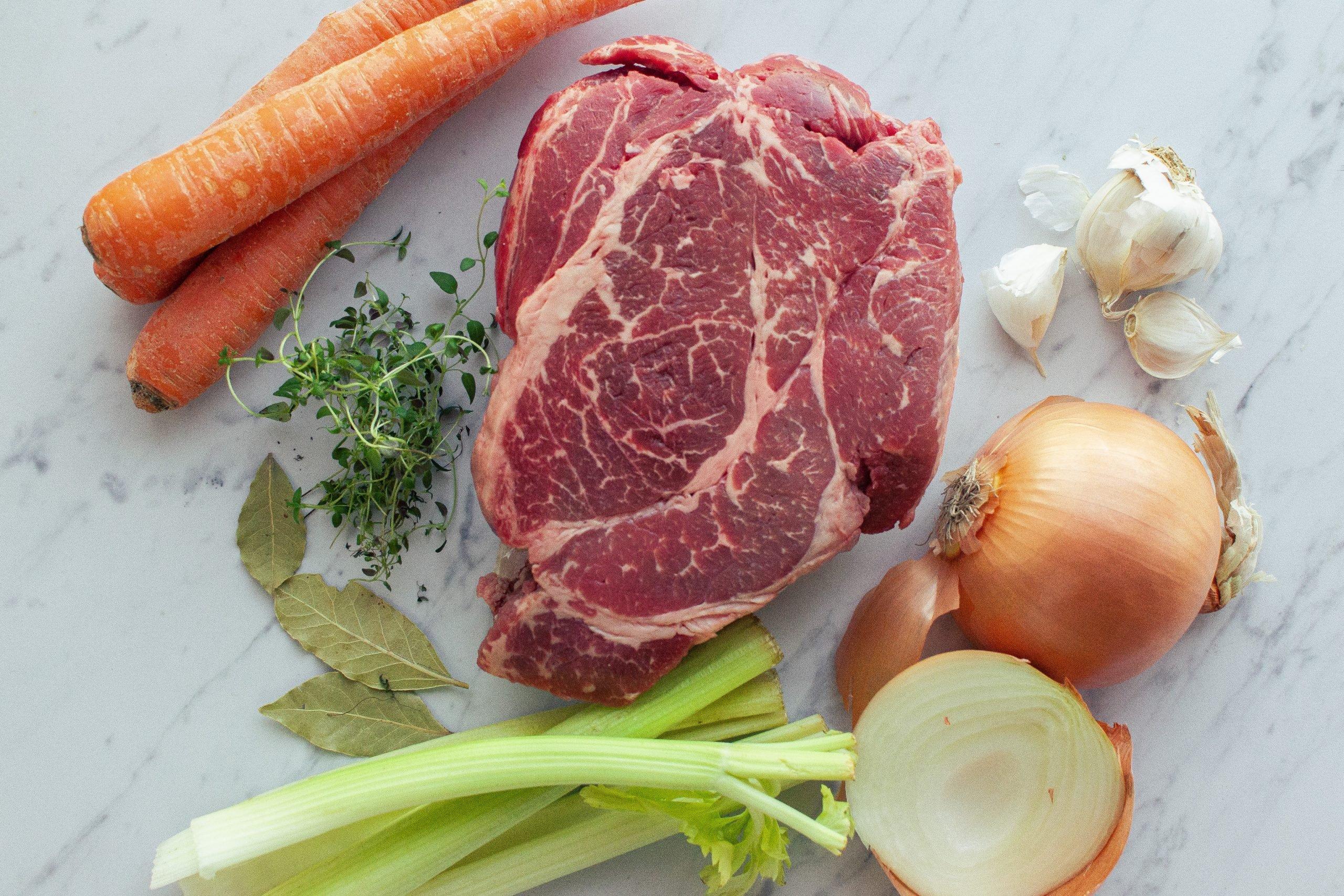 Ingredients for braised beef. Roast, onion, garlic, celery, carrots, thyme, bay leaves