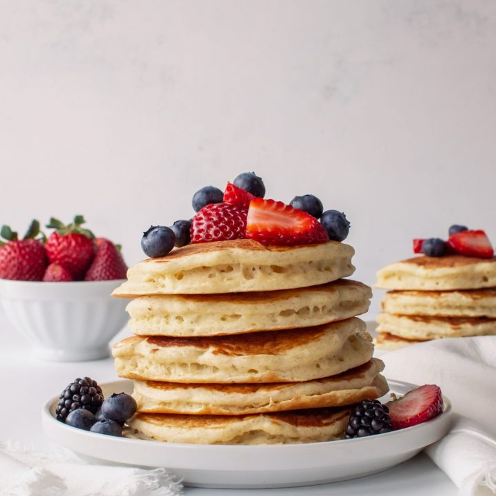 stack of fluffy buttermilk pancakes with fresh fruit