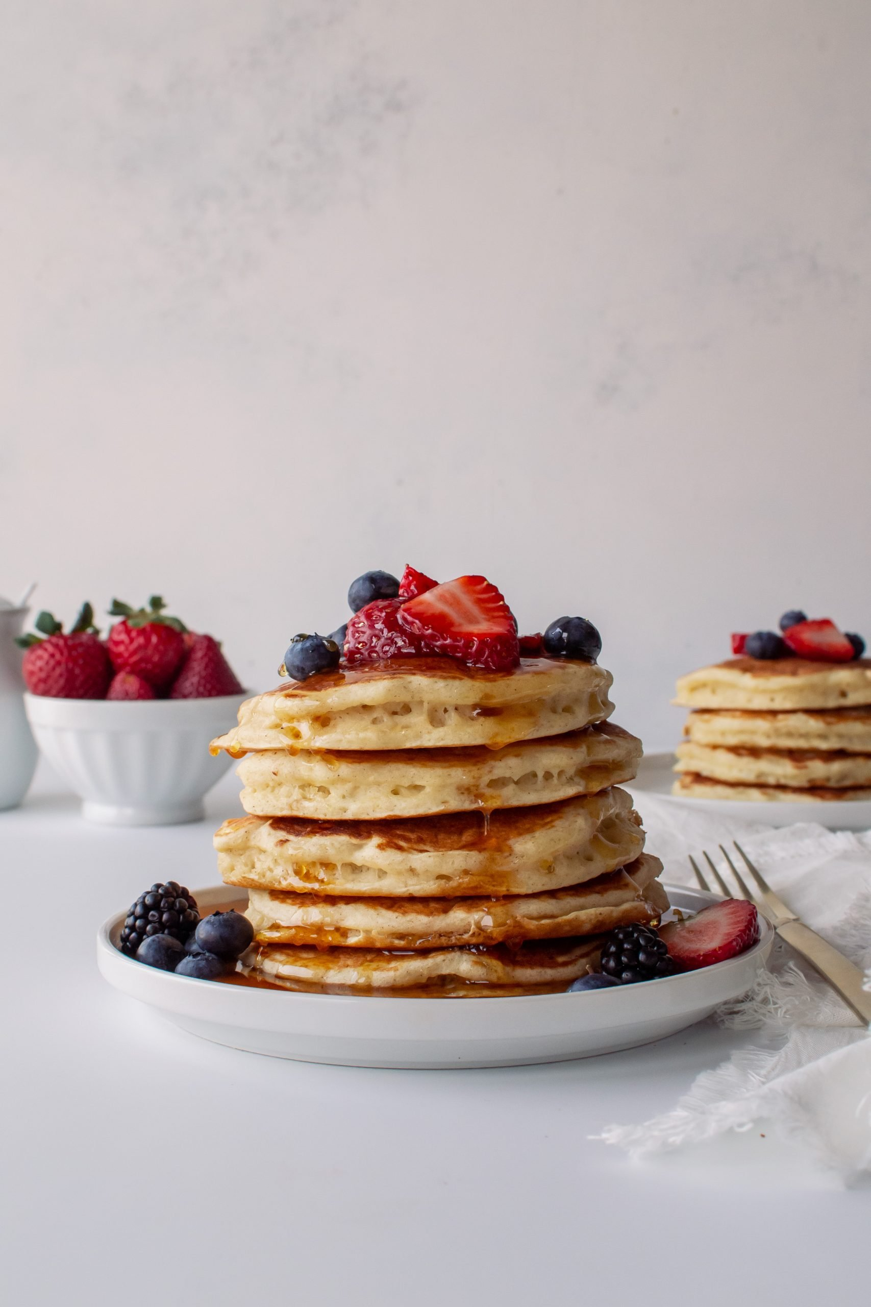 stack of homemade buttermilk pancakes with fresh berries and syrup
