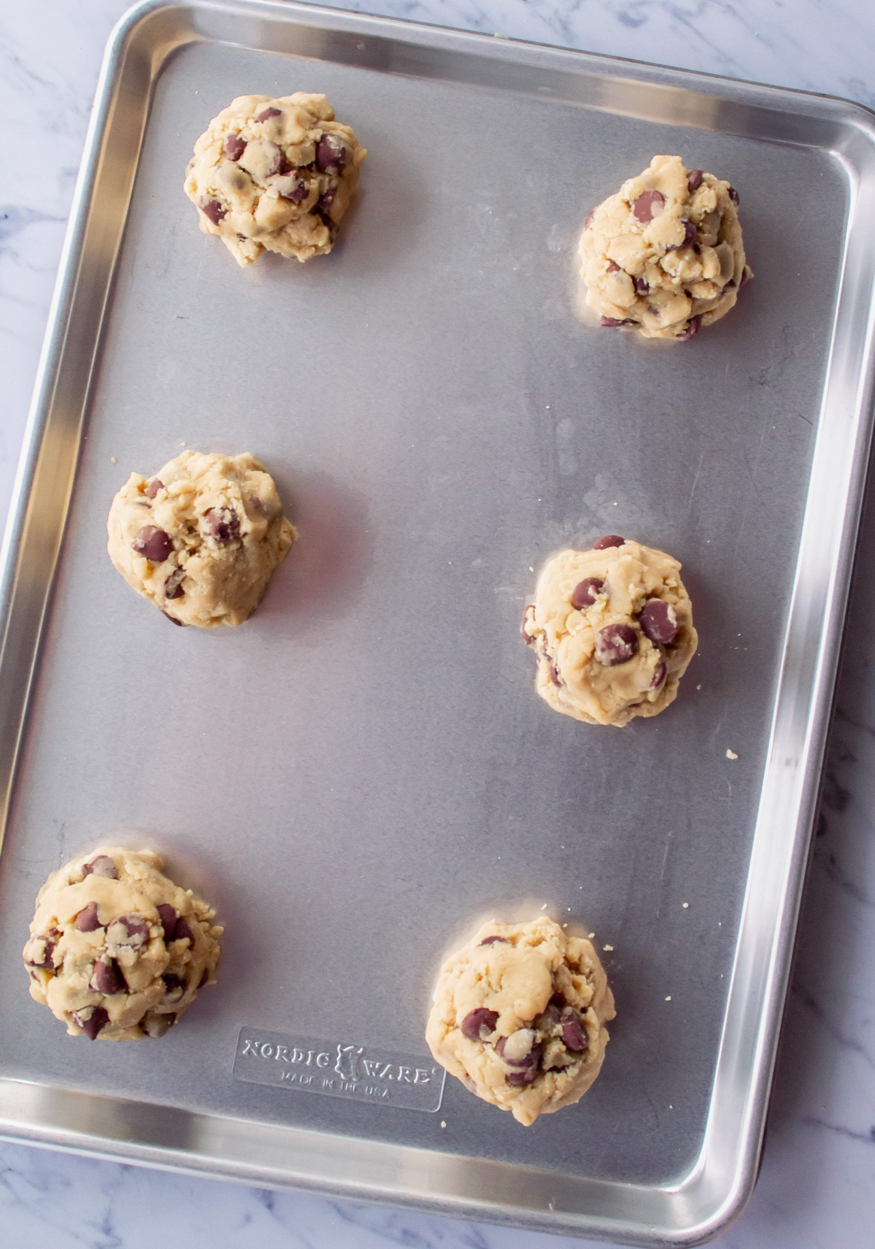 cookie dough balls arranged on cookie sheet for baking