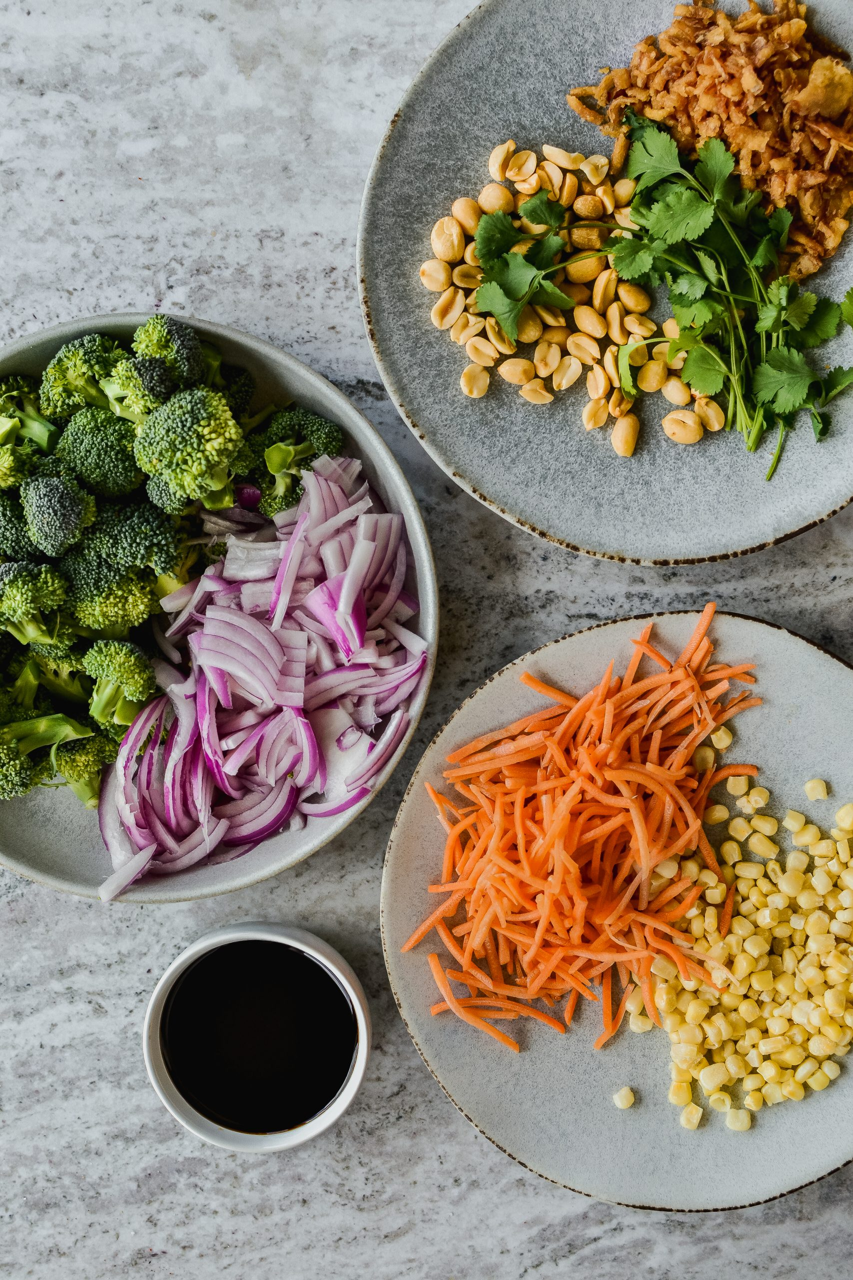 Toppings for rice bowl; roasted broccoli and red onion, shredded carrots, sweet corn, fried onions, peanuts, cilantro, and teriyaki sauce